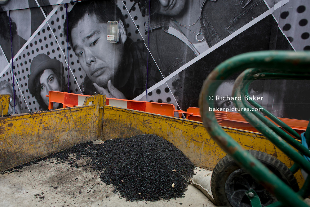 The faces on a construction site hoarding peer over a contractor's pile of tarmac in the back of a small truck.