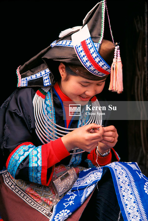 Tip-Top Miao girl doing embroidery work, Guizhou Province, China