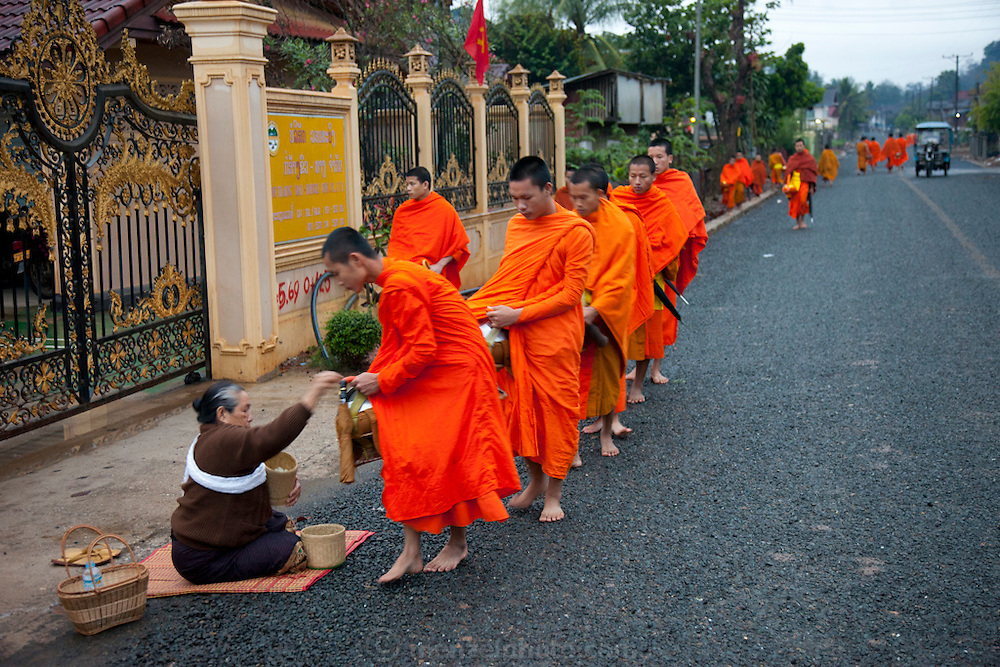 "In Ban Phan Luang, across the Nam Khan River from Luang Prabang, Laos. Every morning at dawn, Buddhist monks walk down the streets collecting food alms from devout, kneeling Bhddhists, and some tourists. They then return to their temples (also known as ""wats"") and eat together. This procession is called Tak Bat, or Making Merit."