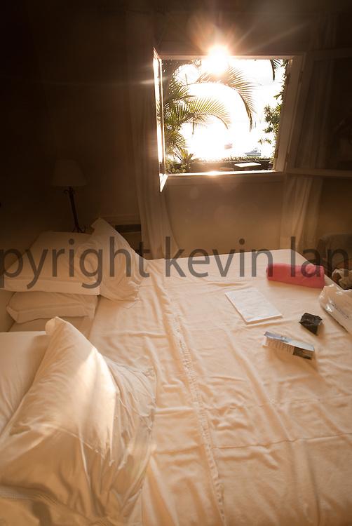 sunset light shines through an open window at a resort posada in buzios, rio de janeiro, brazil