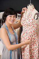 Young fashion designer adjusting dress on the dummy