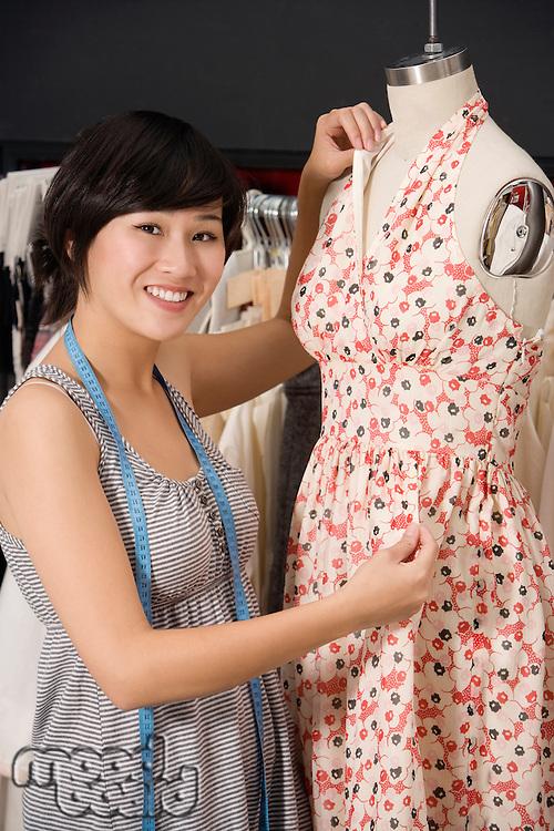 Young fashion designer adjusting dress on the dummy