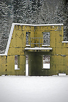 Contrast of a derelict, yellow building against the white snow and snow-covered branches of trees.