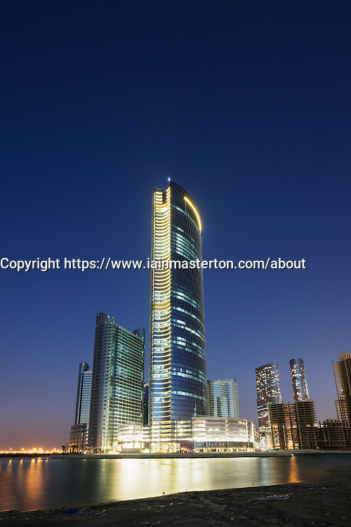 Night view  of modern skyscrapers under construction at new business district called City of Lights on Al Reem Island in Abu Dhabi United Arab Emirates