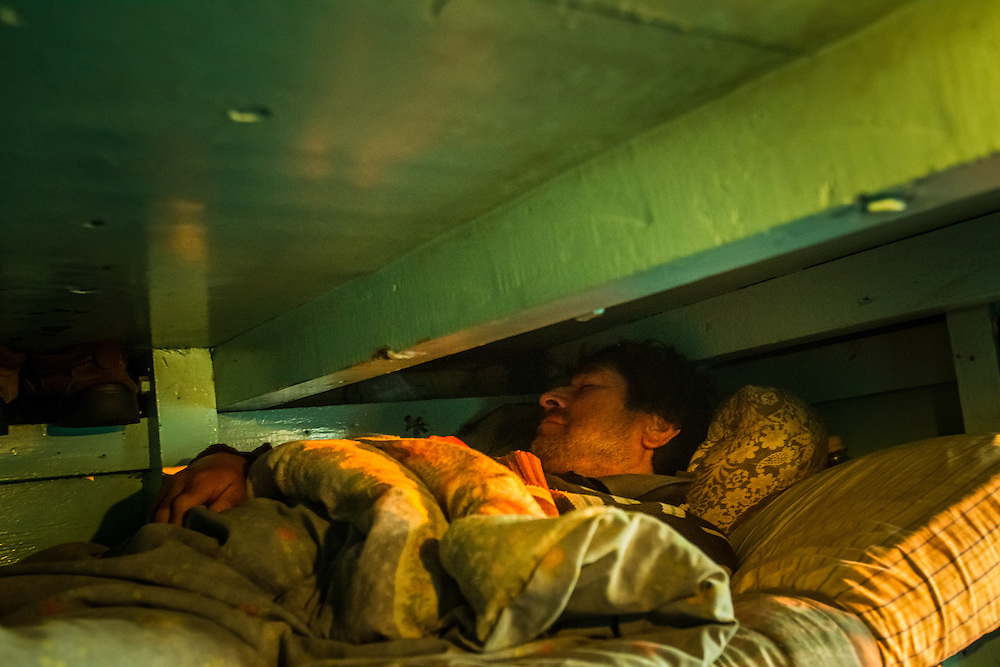CONCEPCION, CHILE - MARCH 20, 2014: Gregorio Pastillas, 41, sleeps in a bunk bed aboard an artisanal fishing boat as dawn breaks, as he and the rest of the boat's crew head two hours off the Pacific coast of Chile from the port in Concepción, to fish for Southern hake (Merluccius australis).  PHOTO: Meridith Kohut for The World Wildlife Fund