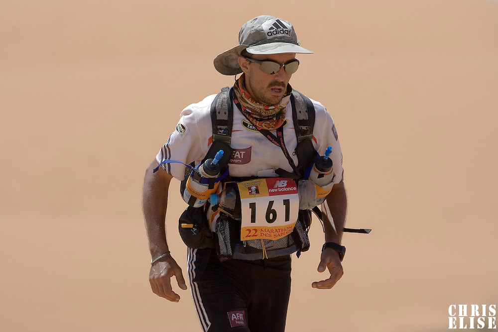 30 March 2007: #161 Herve Demirdjian of France climbs a dune in erg Znaigui en route to check point 3 during fifth stage of the 22nd Marathon des Sables between west of Kfiroun and erg Chebbi (26.22 miles). The Marathon des Sables is a 6 days and 151 miles endurance race with food self sufficiency across the Sahara Desert in Morocco. Each participant must carry his, or her, own backpack containing food, sleeping gear and other material.