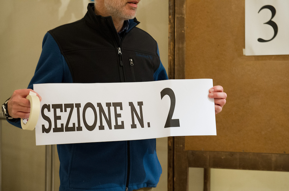 VENICE, ITALY - FEBRUARY 24:  A member of the polling station hold a station number ahead of the official opening on February 24, 2013 in Venice, Italy. Italians are heading to the polls today to vote in the elections, as the country remains in the grip of economic problems . Pier Luigi Bersani's centre-left alliance is believed to be a few points ahead of the centre-right bloc led by ex-Prime Minister Silvio Berlusconi.  (Photo by Marco Secchi/Getty Images)
