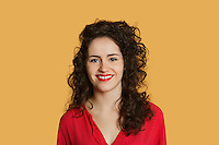 Portrait of a happy young woman with curly hair over colored background