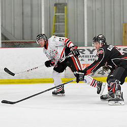"""FORT FRANCES, ON - May 2, 2015 : Central Canadian Junior """"A"""" Championship, game action between the Fort Frances Lakers and the Soo Thunderbirds, Championship game of the Dudley Hewitt Cup. Nicolas Tassone #17 of the Soo Thunderbirds and A.J. Kapcheck #4 of the Fort Frances Lakers follow the shot during the third period.<br /> (Photo by Shawn Muir / OJHL Images)"""