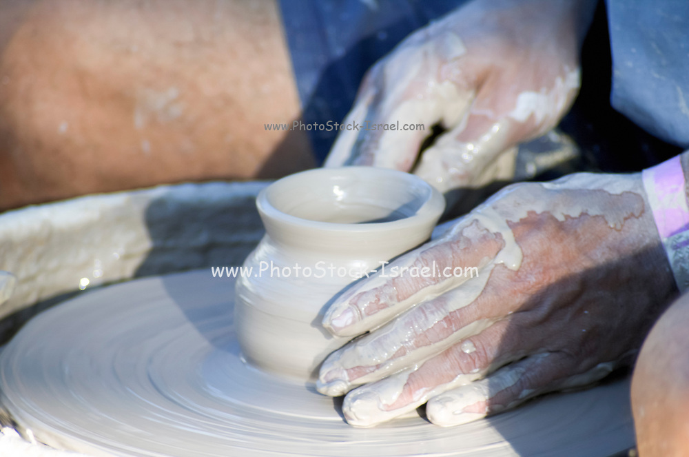 Man making a clay pot on a potter's wheel
