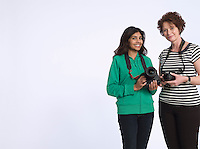 Portrait of two women holding digital cameras studio shot