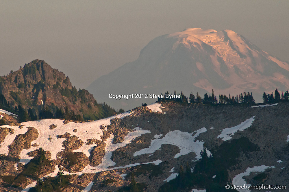 Painted in smoke-tinged light, Mount Adams rises above the Tatoosh Range of Mount Rainier National Park, Washington.
