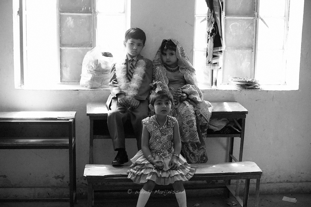 A young boy and girl dressed up as a bride and groom are sitting on a bench in the local girl school waiting for their performance of a play in child brides and child marriages. Even after passing a law banning this practice locally known as Vani, in lots of rural areas the tradition is still very common. Village 109, Khanpur, Pakistan 2010