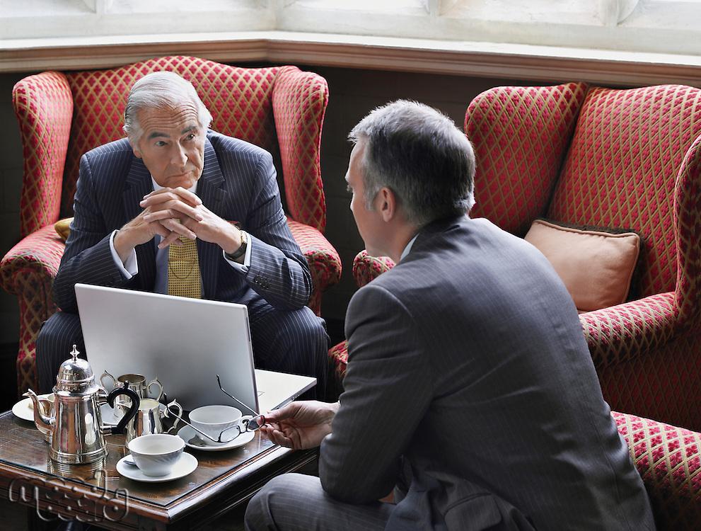 Two business men talking over laptop in lobby