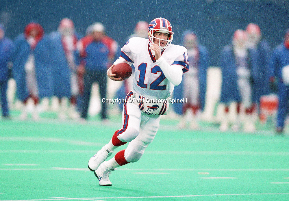Buffalo Bills quarterback Jim Kelly (12) runs the ball in the pouring rain during the NFL football game against the New York Giants on Dec. 15, 1990 in East Rutherford, N.J. The Bills won the game 17-13. (©Paul Anthony Spinelli)
