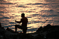 man fishing at sunset above  Sosua Beach, Dominican Republic..Photo by Owen Franken.