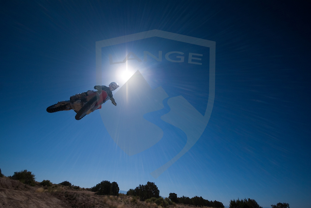 motorcycle rider chris boice jumping with sun in the sky.  taken at west mesa moto tracks on the western fringe of albuquerque, new mexico.