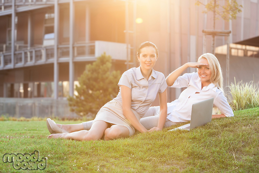 Young businesswomen with laptop relaxing on office lawn