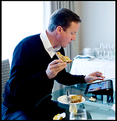 The Prime Minister David Cameron has a piece of toast and checks the web on an Ipad in his hotel room at the Conservative Party Conference in Birmingham, Tuesday October 5,  2010. The Prime Minister is going to receive a personalised iPad app to help him stay on top of Government business. Photo By Andrew Parsons/ i-Images  ..Byline Mandatory
