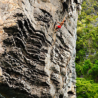 """Climber """"deep water soloing"""" without rope, high above the sea.  Poda Island, Krabi, Thailand"""