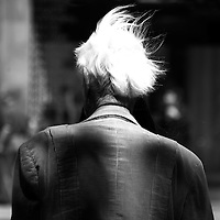 An elderly man standing on a street corner, his white hair flying in the wind.