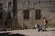 A father pushes a child through early morning light on the walls of old architecture off Place de la Canourge in old Montpellier, south of France.