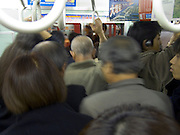 straphangers in an overcrowded train during rush hour Tokyo Japan