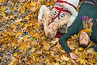 High angle portrait of young couple lying on autumn leaves at park