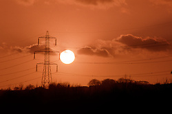 Sun sets behind power lines, Rother Valley, Sheffield, South Yorkshire, England, UK.