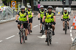 © Licensed to London News Pictures. 07/07/2014. London, UK. Police cyclists ride the route ahead of full road closure on the Highway approach to Tower Hill in East London as roads are closed in preparation for the Tour de France Stage 3 in London today. Photo credit : Vickie Flores/LNP