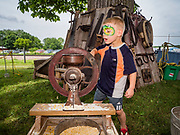 27 JUNE 2019 - CENTRAL CITY, IOWA: AUGUST STEFFEN, 4, grinds corn in an antique grinder at the pioneer life display at the Linn County Fair. Summer is county fair season in Iowa. Most of Iowa's 99 counties host their county fairs before the Iowa State Fair, August 8-18 this year. The Linn County Fair runs June 26 - 30. The first county fair in Linn County was in 1855. The fair provides opportunities for 4-H members, FFA members and the youth of Linn County to showcase their accomplishments and talents and provide activities, entertainment and learning opportunities to the diverse citizens of Linn County and guests.        PHOTO BY JACK KURTZ
