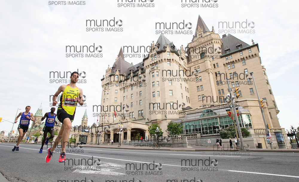 (Ottawa, Canada---24 May 2015) Rob Watson running past the Chateau Laurier at the start of the marathon during the Tamarack Run Ottawa Race Weekend.