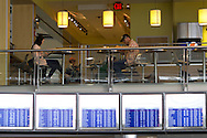 Detroit, Michigan - People sit at tables in a restaurant at Detroit Metropolitan Airport on Feb. 3, 2013. Flight information is shown on screens at the bottom of the photograph.