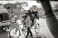 A rickshaw bicyclist and women customers on a street Varanasi (Benares), India.