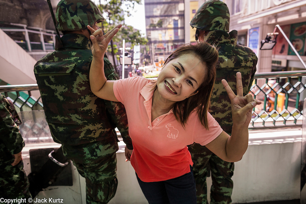 25 MAY 2014 - BANGKOK, THAILAND: A woman poses for photos with Thai soldiers in the background near a shopping mall in Bangkok. There was a much larger military presence on the streets of Bangkok as public opposition to the military coup in Thailand grew Sunday with thousands of protestors gathering at locations throughout Bangkok to call for a return of civilian rule and end to the military junta.     PHOTO BY JACK KURTZ