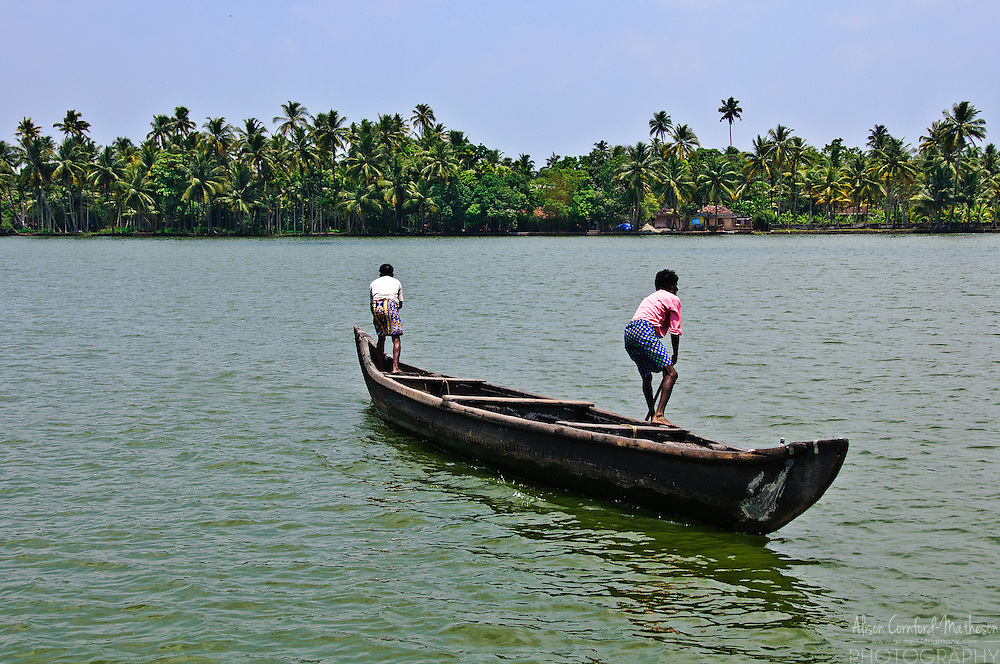 Two men fish from a long boat on the Kerala backwaters