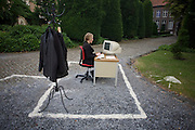 An actor plays the part of an office worker, toiling away at a desk-top PC while outside in the courtyard of the Z33 art gallery in Hasselt, Limburg Belgium. The lady artist sits typing at an imaginary work station with jackets hanging on a coat stand and with her area marked out in sand on the gravel. This incongruous scene is played out during the gallery's 'Werk Nu' (Work Now) exhibition that reflected upon the concept and meaning of 'work' in our present society, with issues such as flexibility, mobility, motivation, significance, and the work-life balance are dealt with. The art works in 'Work Now' are direct or ambiguous, whimsical.