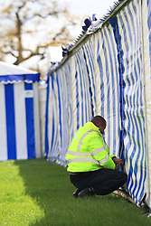 © Licensed to London News Pictures. 30/04/2012. BADMINTON, UNITED KINGDOM. A security guard seals up deserted marquees in the shopping village at The 2012 Mitsubishi Motors Badminton Horse Trials after the announcement that it had been cancelled this morning due to poor ground conditions. The event, which was a key qualifier for the 2012 London Olympic Games, has been called off because of large areas of standing surface water and worries about the going of the Cross Country track. Photo credit: Mark Chappell/LNP
