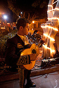 Member of a mariachi band standing alone playing the guitar under trees at night