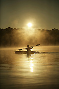 Kayak on a lake with sunrise fog.