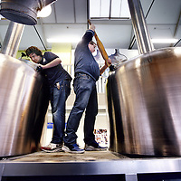 """Nederland, Amsterdam , 12 december 2013.<br /> Bierbrouwerij de Prael.<br /> Leer-werkbedrijf Brouwerij de Prael leidt dit jaar verlies. Zorggelden voor begeleiding nemen af en er is onvoldoende capaciteit om aan de vraag van een groeiende biermarkt te voldoen. """"Doorgroeien is noodzakelijk.<br /> De brouwerij die in 2008 vanwege een ruimtetekort naar de Oudezijds Voorburgwal verhuisde, lijkt nu opnieuw uit zijn voegen gegroeid. De verkoop loopt goed, het Proeflokaal loopt goed. Maar de ruim 130 werknemers met een psychiatrische achtergrond vergen begeleiding, en de zorggelden daarvoor nemen af. """"We krijgen van bijvoorbeeld DWI of GGZ instellingen een derde minder geld. De bijdrage voor individuele begeleiding is weggevallen."""" zegt Fer Kok, bedrijfsleider bij de brouwerij. Tien mensen blijken nu door de verplichte CIZ-indicatie niet te indiceren. De Prael krijgt daarvoor geen vergoeding en ontvangt een ton minder inkomsten per jaar. """"Doordat een vergoeding voor tien mensen wegvalt, draaien wij verlies. Toch wegsturen omdat ze hem niet hebben? Dat krijg ik niet over mijn hart. Over een jaar of drie komen ze dan terug met indicatie en al, maar zijn ze er stuk een stuk slechter aan toe.""""<br /> Op de foto: Bedrijfsleider Fer Kok (r) met 1 van de werknemers met psychiatrische achtergrond aan het werk in de brouwerij.<br /> Beer brewery Prael with employees who need care and learning as psychiatric patients, is loss-making this yea , due by cuts of care money necessary for the supervision."""