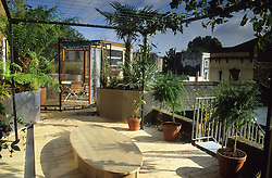 Upper roof terrace. Decking with shallow steel rill, tensioned wire pergola, raised metal beds and dining area with sliding wire mesh screens. Design: Diarmuid Gavin