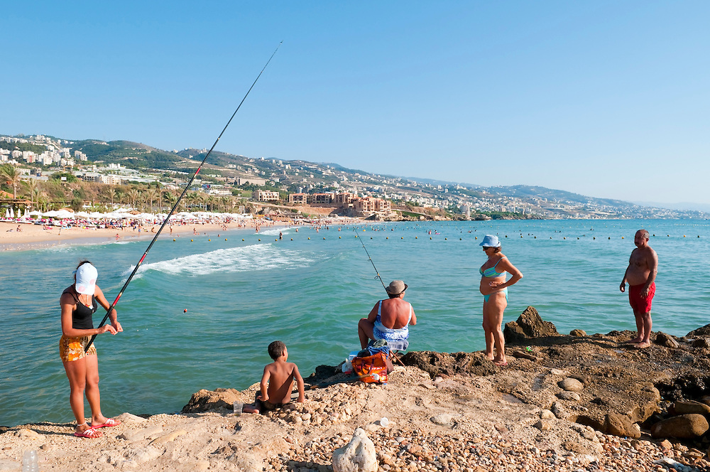 A group of Lebanese, including two women fishing, enjoy a September day at a popular beach beside the ancient Mediterranean city of Byblos, located a few miles north of Beirut. (Byblos, Lebanon - September 4, 2010)