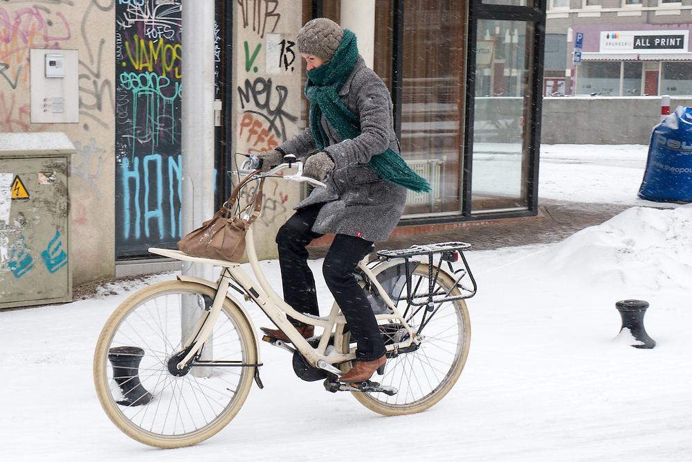 Een meisje fietst tegen de kou in door de sneeuw in Utrecht. De sneeuwval in het westen van land heeft de nodige overlast veroorzaakt.