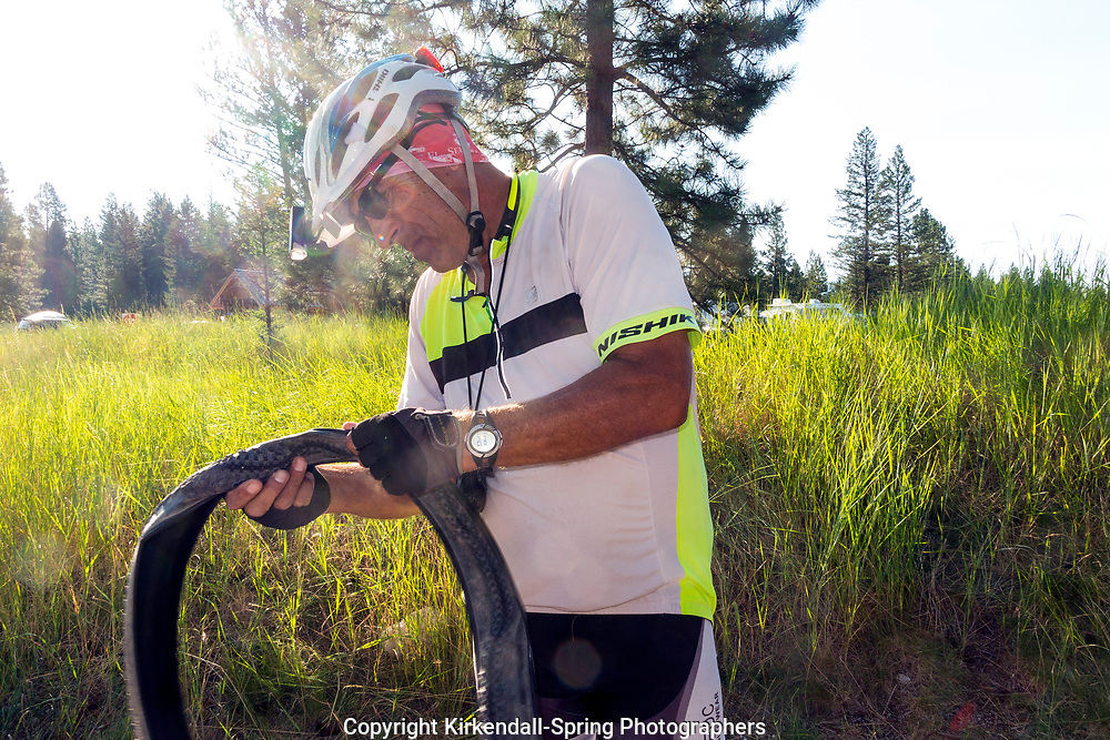 BC00634-00...BRITISH COLUMBIA - George Jackson inspects for tire damage while fixing a flat at the campsite in Kikomun Provincal Park.
