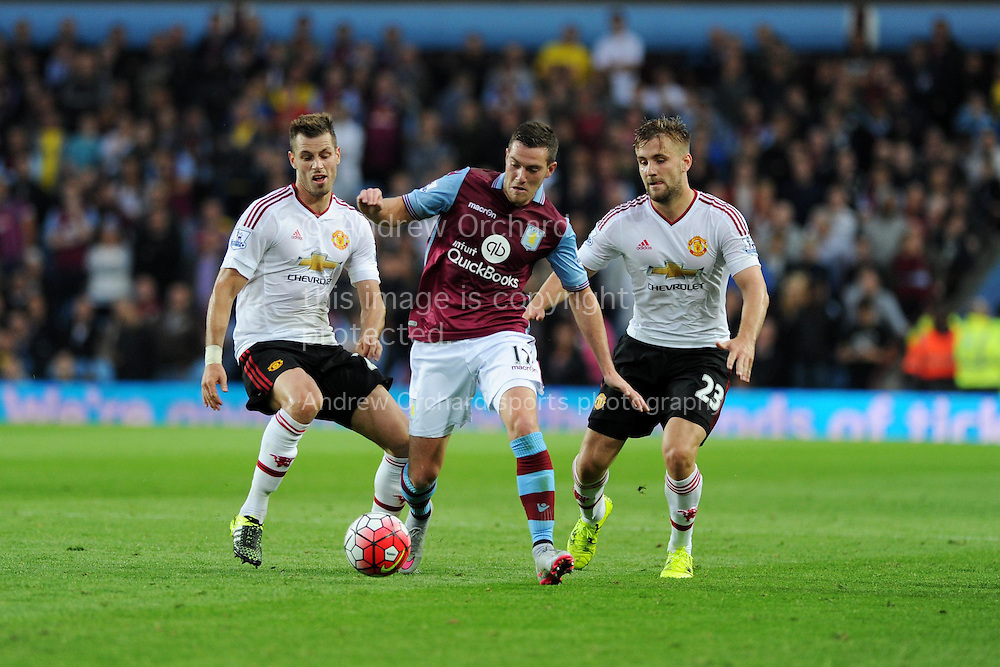 Jordan Veretout of Aston Villa &copy; goes between Morgan Schneiderlin (l) and Luke Shaw of Manchester Utd. Barclays Premier League match, Aston Villa v Manchester Utd at Villa Park in Birmingham, Midlands on Friday 14th August  2015.<br /> pic by Andrew Orchard, Andrew Orchard sports photography.