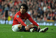 A dejected Carlos Tevez sits on the pitch during the Barclays Premier League match between Manchester United and Liverpool at Old Trafford on March 14, 2009 in Manchester, England.