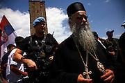 "Serbian anniversary celebrations at the site of the 1389 ""Battle of Kosovo"" near Pristina, Kosovo. Serbian priest guarded by a KFOR soldier...Gazimestan, Kosovo, Serbia."