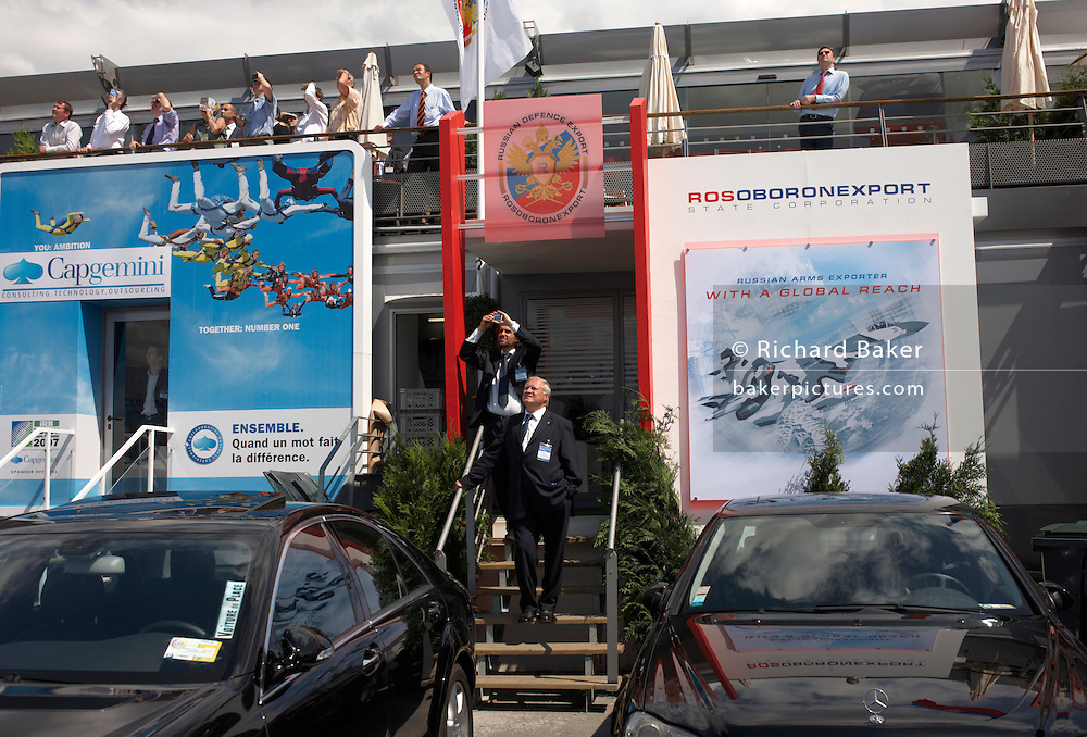 Spectators at the French Capgemini and Russian Defence Export chalets watch flying displays outide during the Paris Air Show