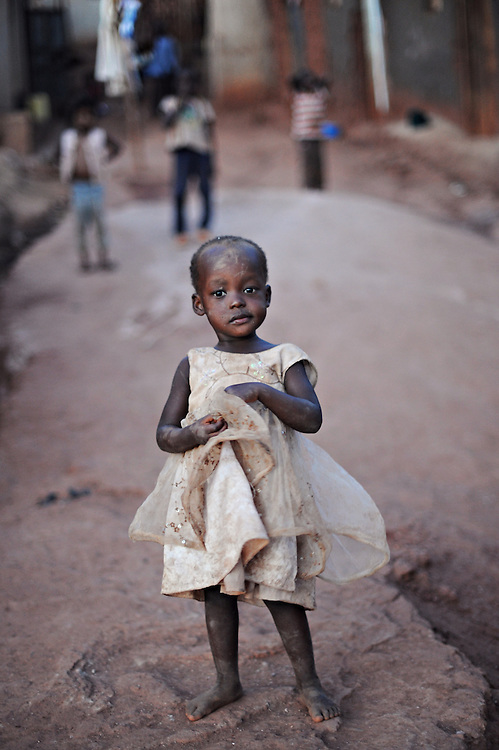 12-03-21   -- KAMPALA, UGANDA --  A young girl stands in the Acholi Quarter slum on March 21, 2012. Fleeing rebel violence in Northern Uganda, thousands of Acholi settled in a rock quarry, where -- to make a living -- they have been mining by hand for over 20 years. Photo by Daniel Hayduk